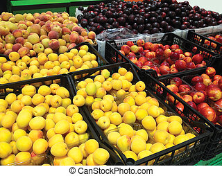 Many fruits apricots, peaches, nectarines and plums lying in boxes in supermarket