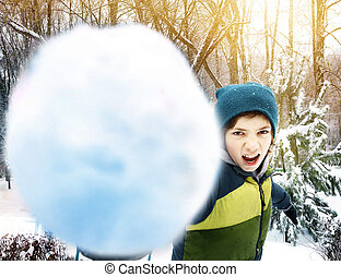 teen boy throwing snow ball outdoor on winter park snowy...