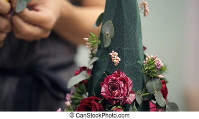 Female hand fills a bouquet florist floral decorations on...