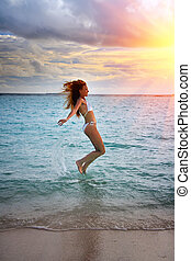 Maldives. The silhouette the slender young woman happily jumps in the sea on a sunset
