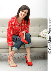 brunette having pain in feet after wearing high-heeled shoes...
