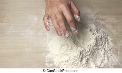 Inserting the yolk into a pile of flour
