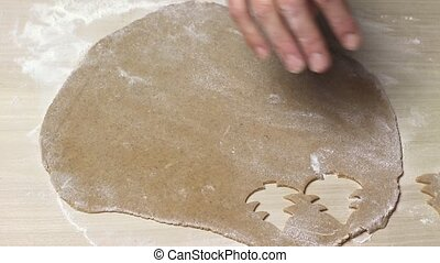 Baking Christmas cookies - Cutting out cookies from rolled...