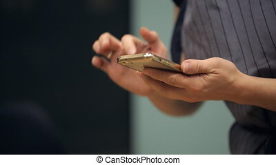 human hands to dial a number on a mobile phone golden color....
