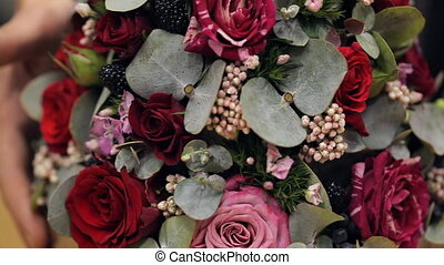Bouquet of red and pink roses, blackberries, small blossoms and green leaves