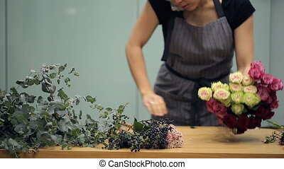 Florist cleans table for new bouquet and takes the order by...