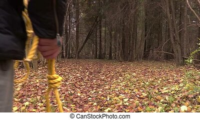 Man with gallows noose walking into the forest
