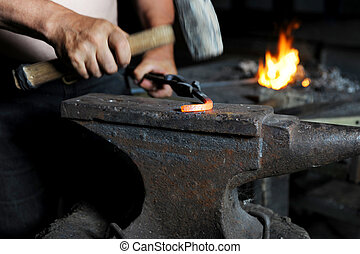 blacksmith forges iron in the forge