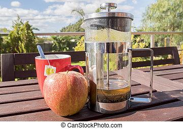Cup of tea with apple, breakfast in the garden