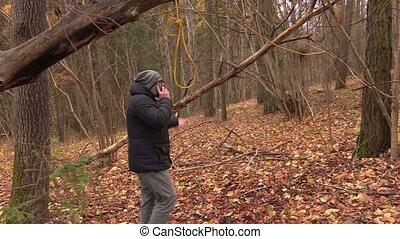 Depressed man talking on phone near gallows noose