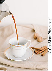 hot black coffee in a white cup on a napkin beige, cinnamon
