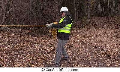 Worker pulling rope in forest