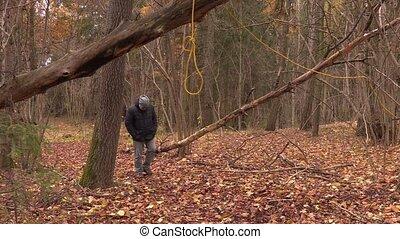 Depressed man walking near gallows noose