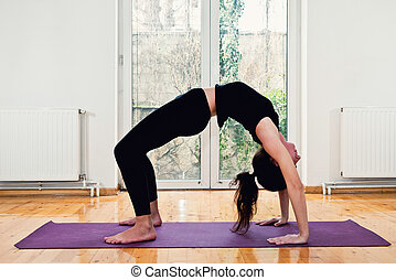 Woman doing Yoga at home - Bridge position. Slightly toned...