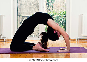 Woman doing Yoga at home - Camel position or Ustrasana -...