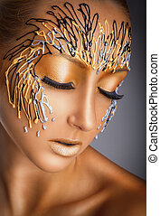 Portrait of a beautiful woman with fantasy gold makeup