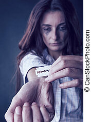 Depression - Young woman cuts veins on a hand on a dark...
