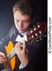 Playing the guitar - Guitarist. Man playing guitar on black...
