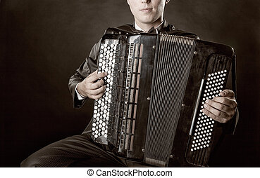 Accordion - Musician playing the accordion against a black...