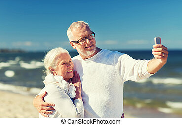 happy senior couple hugging on summer beach - family, age,...