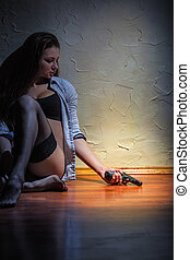 Suicide - Lonely young woman with a gun sitting on the...