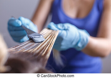 Professional hairdresser dyeing hair of her client in salon....