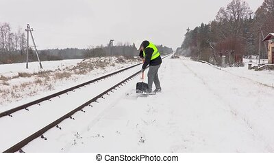 Railroad employee clean snow near the platform