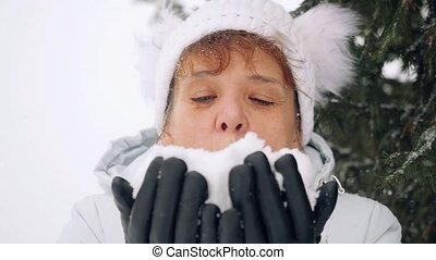 Mature happy woman in age blowing snowflakes in slowmotion...