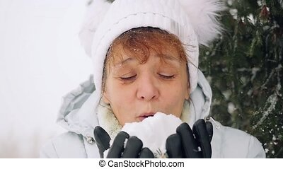 Mature happy woman in aged blowing snowflakes in slow motion...