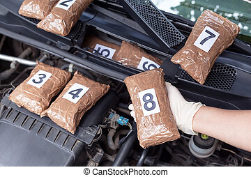 Policeman holding drug package found in engine compartment...