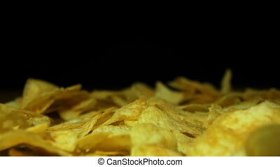 Man Takes the Potato Chips by hand on a Wooden Table on Black Background in Slow Motion
