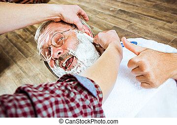 The senior man visiting hairstylist in barber shop. - The...