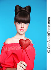 Red heart in teen girl hand. Brunette young model with bow...