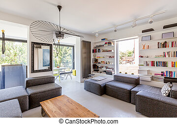Bright living room with couch, table and many books on the...