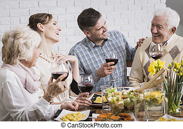 Laughing family during dinner - Laughing members of the...