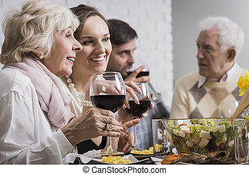 Women drinking wine during family dinner - Two smiling women...