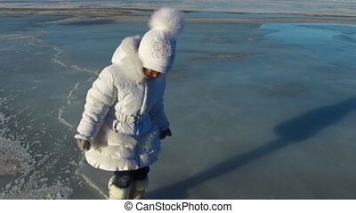 Girl child walks on the ice large lake. Girl is glad that...