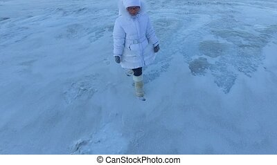 Girl child leaves the frozen lake. The child goes home with disappointment. Girl would like to take a walk on the ice yet. Frosty winter day