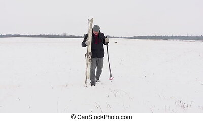 Man with pair of ski on snowy field