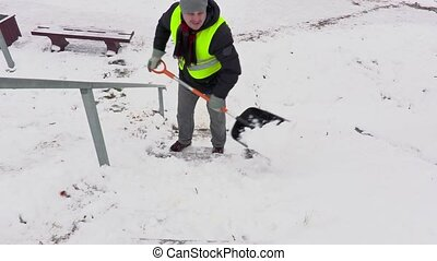 Janitor with snow shovel cleaning stairs