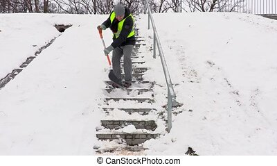 Janitor with snow shovel stepping down and cleaning stairs