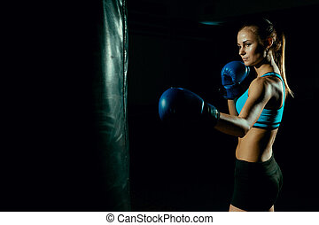 Young woman in blue boxing gloves.