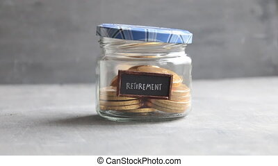 Retirement tag and coins in a glass jar. Save money fund...