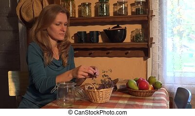 young woman assort herbal thyme glass jar in rural kitchen....