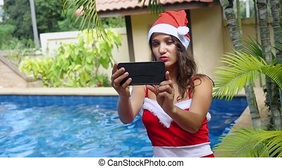 Young sexy woman in red santa claus hat making self portrait...
