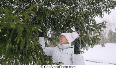 Happy mature woman in aged shaking snowy branches in slowmotion has a fun.