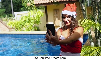 Young beautiful woman in red santa claus hat making self...