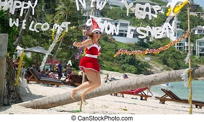 Young woman jump on the beach in santa's hat and dress in...
