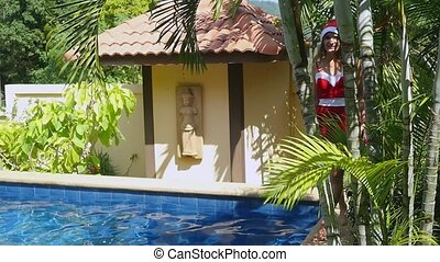 Young woman in dress and santa hat look out from palm tree...