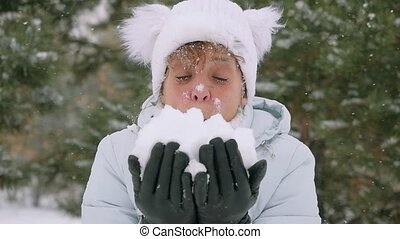 Mature smiles woman in age throwing snowflakes in slowmotion...